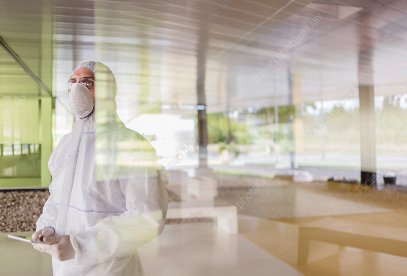 Scientist in clean suit using tablet at window