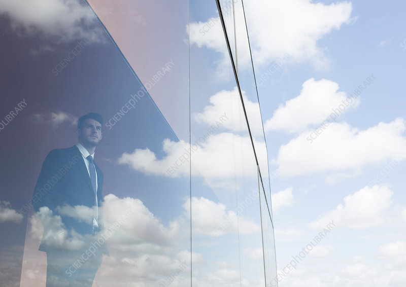 Businessman looking out modern office window
