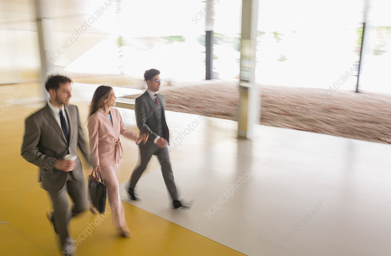 Business people walking in office lobby