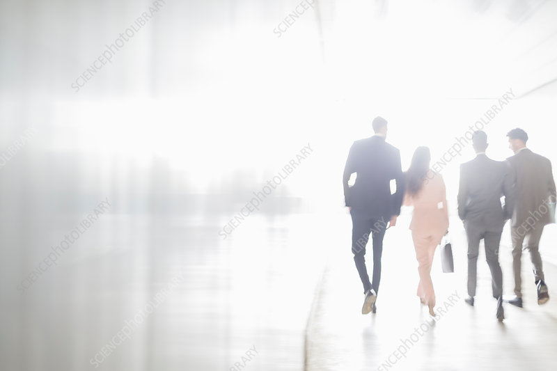 Business people walking in sunny office corridor