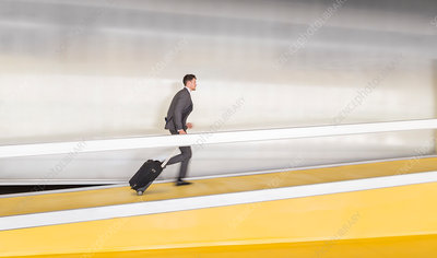 Businessman pulling suitcase up airport ramp