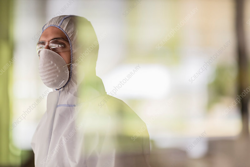 Pensive scientist in clean suit looking away