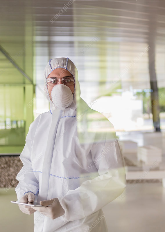 Portrait scientist in clean suit using tablet