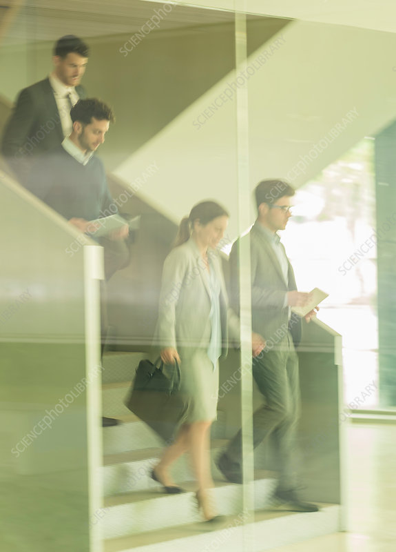 Business people walking, descending stairs