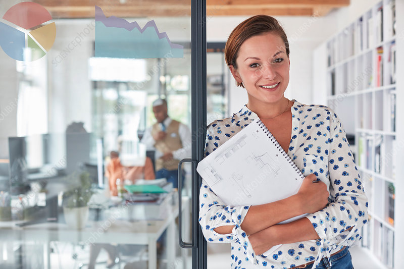 Portrait confident businesswoman with notebook