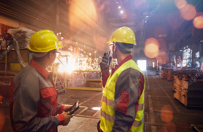 Steelworkers with walkie-talkie watching welding