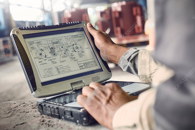 Engineer using laptop, reviewing blueprints