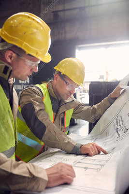Engineer and steelworker discussing blueprints