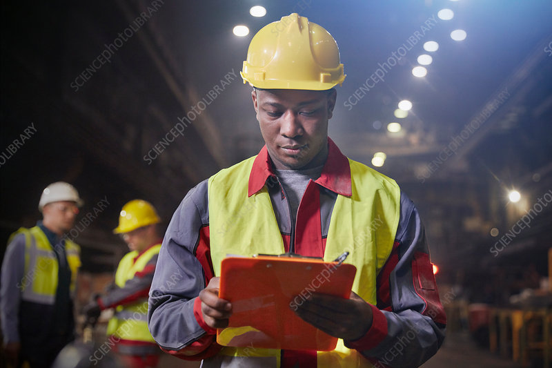 Steelworker with clipboard working in steel mill