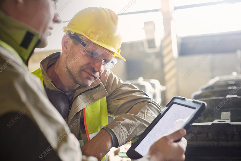 Steelworkers using digital tablet in steel mill