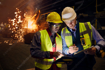Steelworkers using digital tablets in steel mill