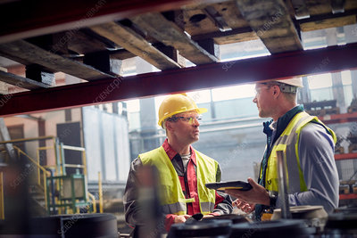 Steelworkers with tablet talking in steel mill