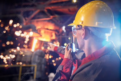 Steelworker talking, using walkie-talkie