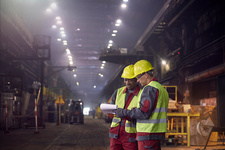 Steelworkers with clipboard meeting in steel mill