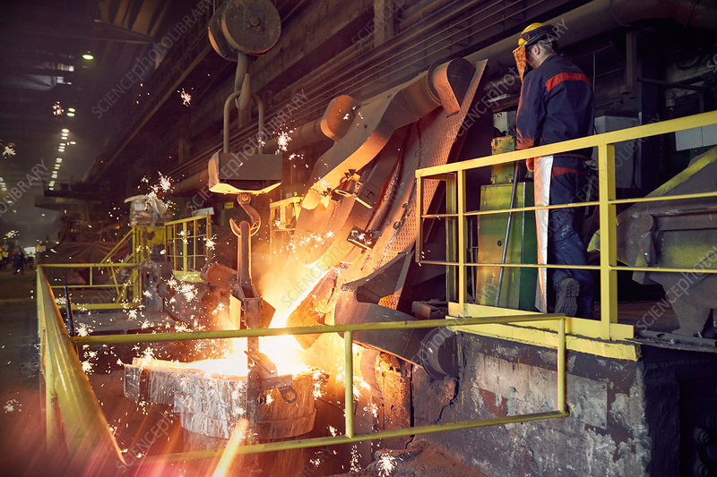 Steelworker on platform above molten furnace