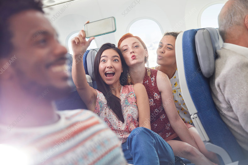 Playful friends taking selfie on airplane