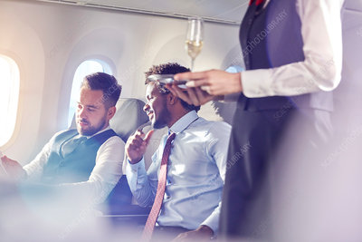 Flight attendant serving champagne to businessmen