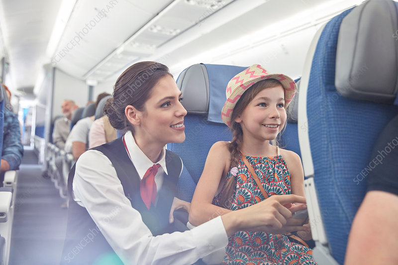 Female flight attendant helping girl on airplane