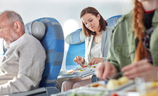 Woman eating dinner on airplane