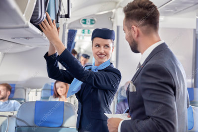 Flight attendant helping businessman with luggage