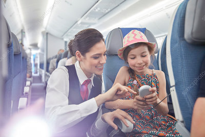 Flight attendant helping girl passenger
