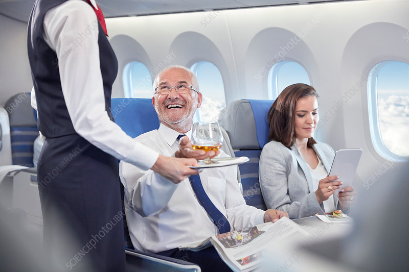 Flight attendant serving whiskey to businessman
