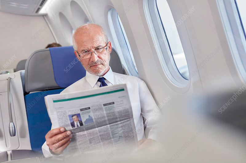 Businessman reading newspaper on airplane