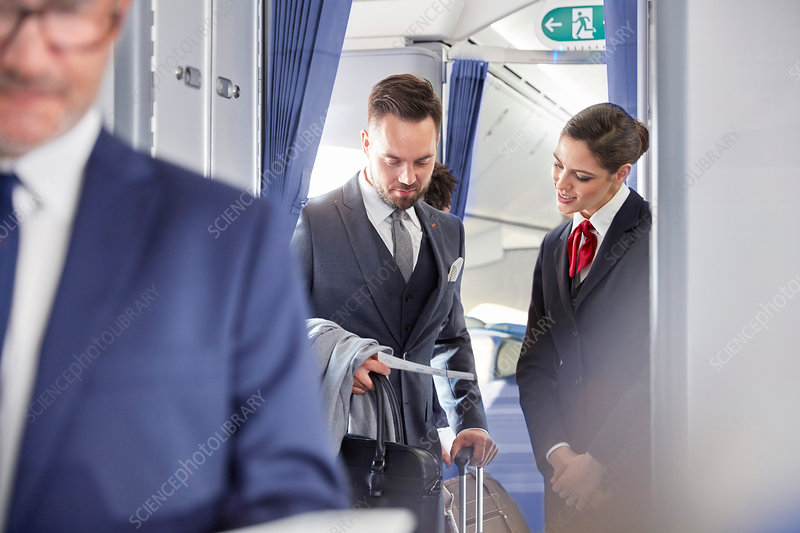 Flight attendant helping businessman