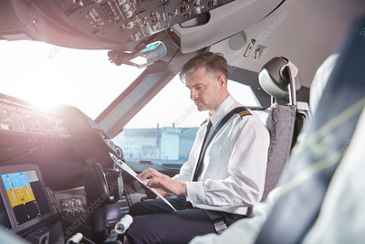 Male pilot preparing in airplane cockpit