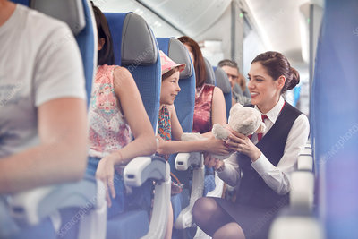 Girl showing teddy bear to flight attendant