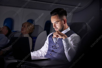 Serious businessman working on overnight airplane