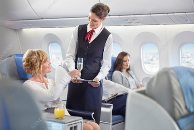 Flight attendant serving champagne to woman