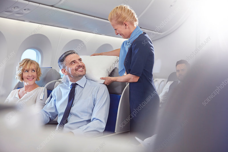 Smiling flight attendant adjusting pillow