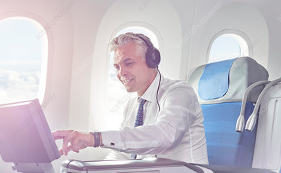 Businessman watching movie on airplane