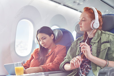 Young women friends and digital tablet on airplane