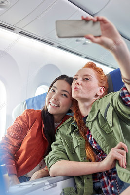 Young women friends posing for selfie on airplane