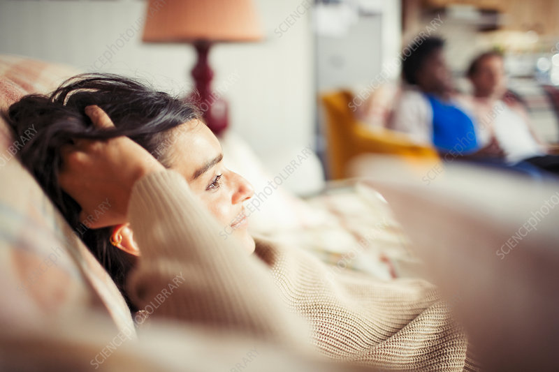 Young woman relaxing with hand in hair on sofa