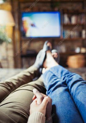 Couple holding hands watching TV