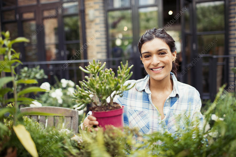 Portrait woman gardening with potted plants