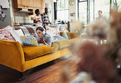 Young woman using laptop on living room sofa