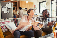 Men friends playing video game in living room