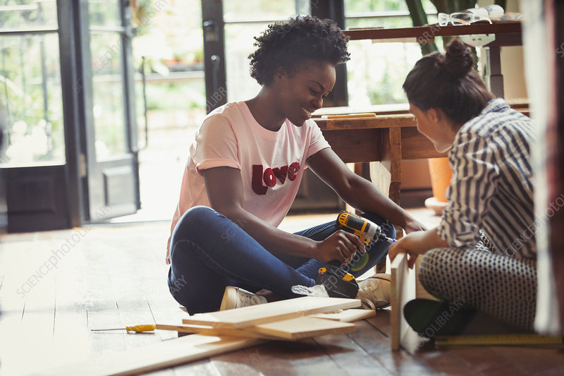 Women assembling furniture with power drill