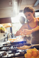 Young woman cracking egg over skillet on stove