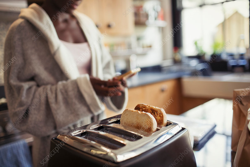 Woman texting, toasting bread in toaster