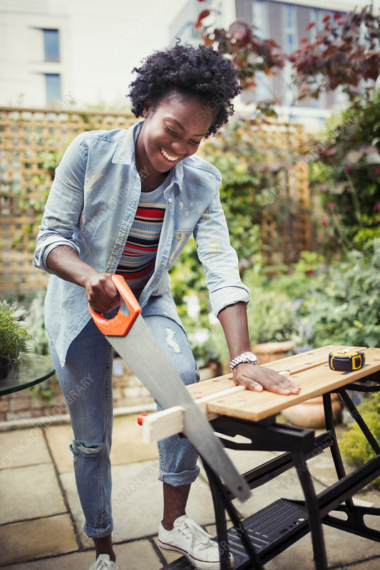 Smiling woman with saw cutting wood on patio