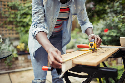 Woman with tape measure measuring wood on patio