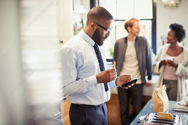 Businessman eating breakfast and texting