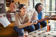 Laughing women friends playing video game