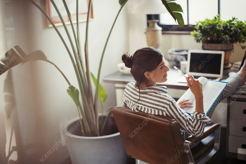 Businesswoman reading paperwork with feet up