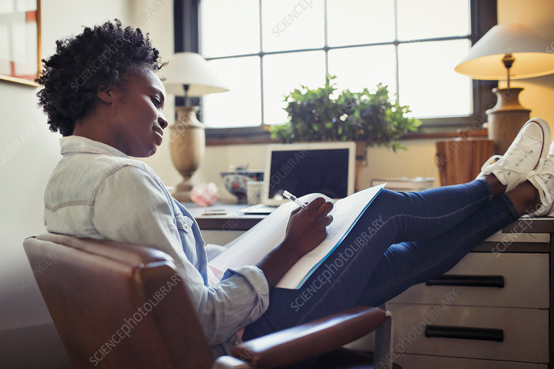 Businesswoman reviewing paperwork with feet up